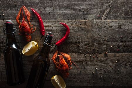 top view of red lobsters, lemon slices, pepper and bottles with beer on wooden surface
