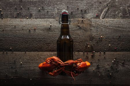 top view of red lobsters on bottle with beer at wooden surface