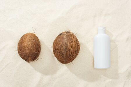 flat lay with white sunscreen lotion and coconuts on golden sand Reklamní fotografie