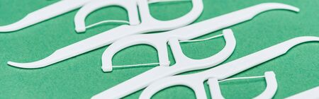 panoramic shot of white and plastic floss toothpicks isolated on green Imagens