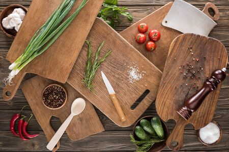 top view of cutting boards, cherry tomatoes, salt, garlics, cucumbers, chili peppers, pepper mill, spoon, meat chopper, knife and spices
