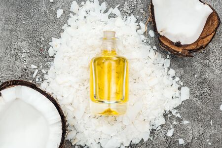 top view of coconut oil in bottle on grey textured background with coconut shavings