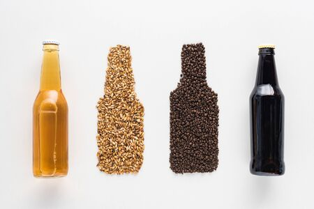 top view of bottles of dark and light beer near wheat and coffee grains isolated on white Stock Photo