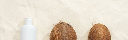 top view of coconuts and white sunscreen lotion on sand, panoramic shot Stock Photo