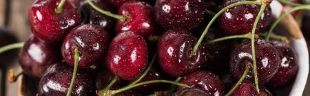 panoramic shot of fresh, sweet, red and ripe cherries covered with water drops
