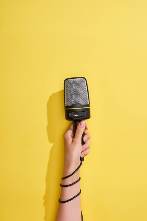 cropped view of woman holding microphone on yellow background 版權商用圖片 - 130303442