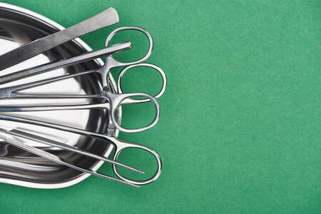 top view of scissors and dental tools in metallic plate isolated on green