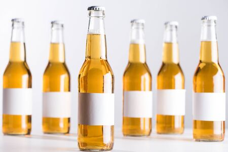 selective focus of glass beer bottles with blank white labels isolated on grey Stock Photo