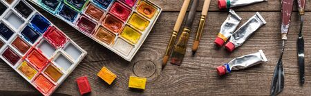top view of colorful paint palettes and drawing tools on wooden surface, panoramic shot Banco de Imagens
