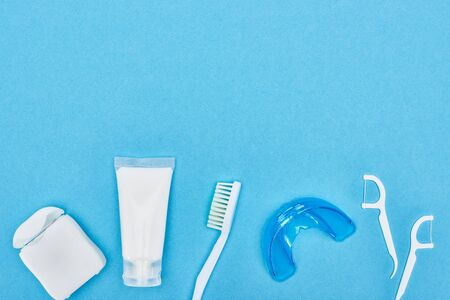 top view of toothpaste, toothbrush and teeth floss near retainer and floss toothpicks isolated on blue