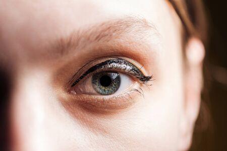 close up view of young woman eye with eyelashes and eyebrow looking at camera