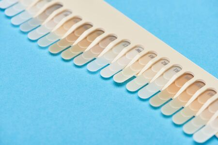 selective focus of teeth palette with different shades isolated on blue