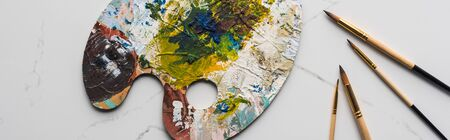 top view of colorful palette with oil paints near paintbrushes on marble white surface, panoramic shot Banco de Imagens - 130305954