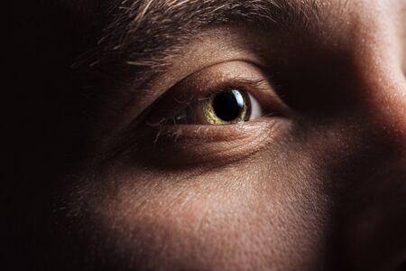 Vista de cerca del ojo del hombre adulto apartar la mirada en la oscuridad