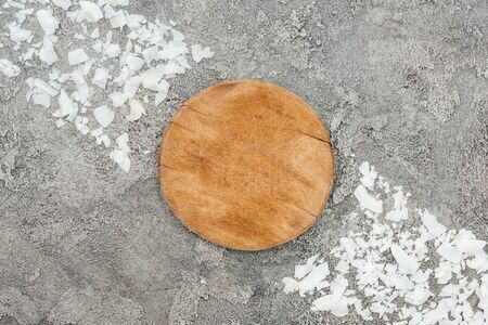 top view of coconut shavings near wooden board on grey textured background Фото со стока