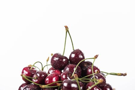 red, fresh, whole and ripe cherries covered with water drops