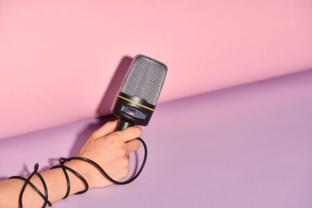 cropped view of woman holding loudspeaker on colorful background