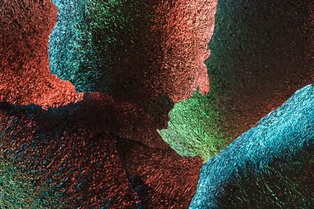 abstract background of shiny textured foil pieces with colorful illumination