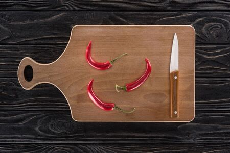 top view of cutting board, knife and chili peppers on table