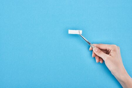 cropped view of woman holding tweezers with cotton pad on blue