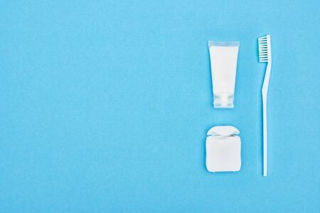 top view of toothbrush and toothpaste near dental floss isolated on blue