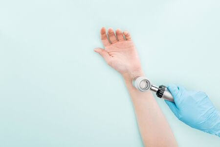 cropped view of doctor examining hand of woman with dermatoscope isolated on blue 版權商用圖片