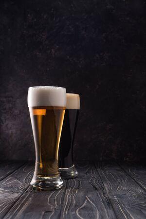glasses of fresh light and dark beer on wooden table 版權商用圖片