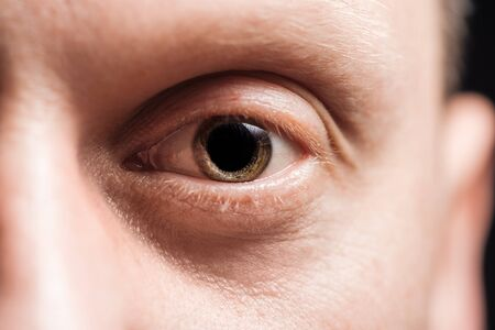 close up view of adult man eye looking at camera