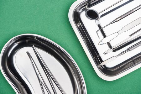 top view of set with dental tools in metallic plates isolated on green