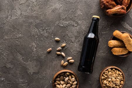 top view of bottle of dark beer near bowls with nuts and chicken snacks on brown surface