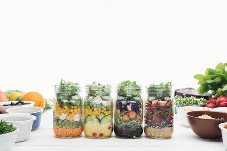 Ensalada de verduras frescas en frascos de vidrio sobre mesa de madera blanca aislado en blanco