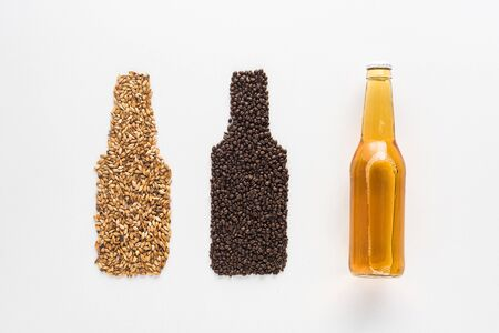 top view of bottle of light beer near wheat and coffee grains isolated on white