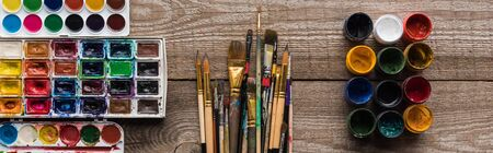 top view of colorful paint palettes on wooden brown surface with paintbrushes and gouache, panoramic shot 版權商用圖片