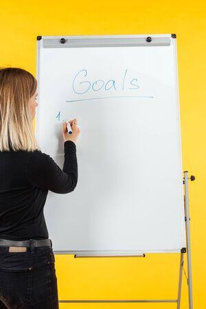 Vista posterior de la empresaria de pie cerca del rotafolio blanco, escribiendo la lista de objetivos