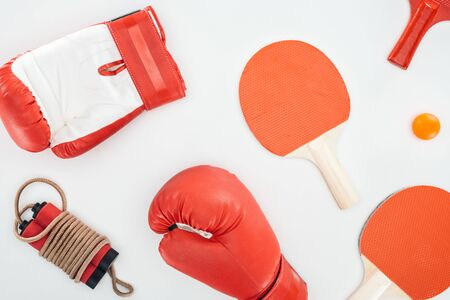 top view of boxing gloves near red table tennis rackets and skipping rope isolated on white Zdjęcie Seryjne