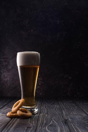 glass of fresh light beer near fried onion rings on wooden table Foto de archivo - 130309763
