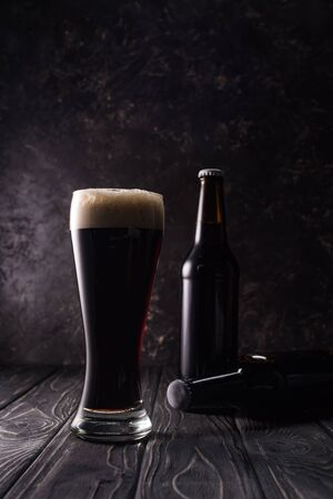 bottles and glass of beer in shadow on wooden table Stock Photo
