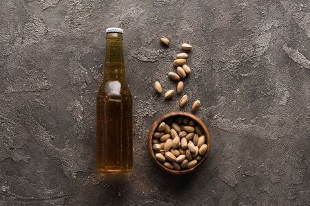 top view of bowl with pistachios near bottle of light beer on brown surface Standard-Bild