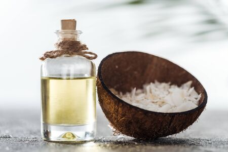 selective focus of bottle with coconut oil near coconut shell with coconut shavings