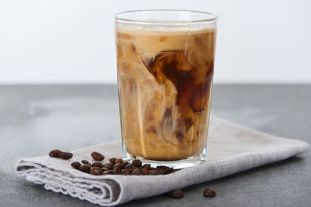 ice coffee mixing with milk in glass on napkin with coffee grains isolated on white Stock Photo