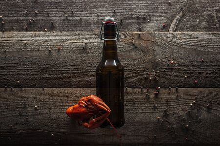 top view of red lobster and bottle with beer on wooden surface Stock Photo