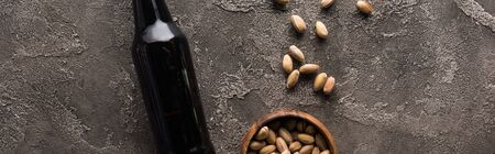 panoramic shot of bottle of dark beer near pistachios on brown textured surface Stock Photo