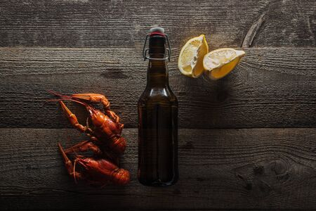 top view of red lobsters, lemon slices and bottle with beer on wooden surface