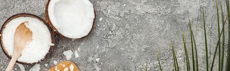 top view of coconut halves and flakes on grey textured background with copy space, panoramic shot