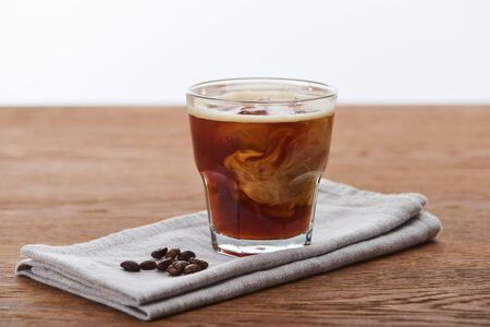 ice coffee mixing with milk in glass on napkin with fesh coffee grains on wooden table isolated on white