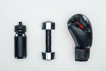 top view of black sport bottle near dumbbell and boxing glove isolated on white