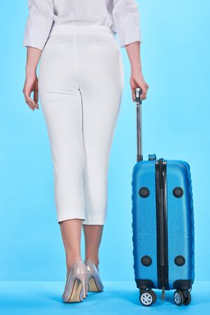 back view of woman holding handle of blue colorful travel bag on blue background