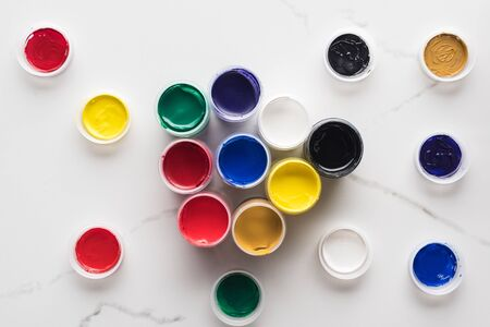 top view of multicolored gouache paints on marble white surface
