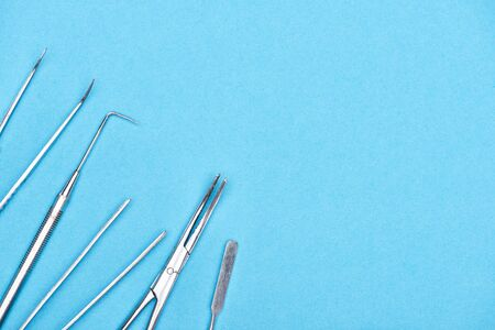 top view of set with stainless dental instruments isolated on blue