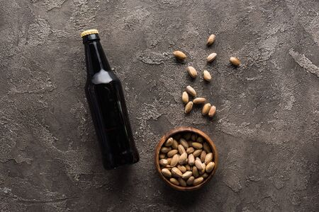 top view of bowl with pistachios near bottle of dark beer on brown surface
